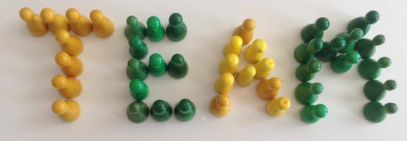 Gelbe und grüne Spielfiguren sind zu dem Begriff Team aufgestellt.
