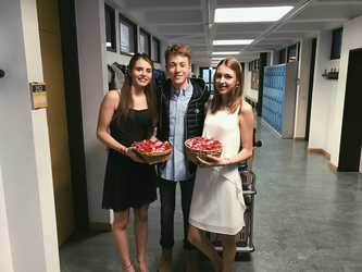 Auf der Fotografie sind zwei Schülersprecherinnen und in der Mitte ein Schülersprecher zu sehen. Sie stehen in einem Schulflur vor einer Klassentür. Die drei sind sehr schick gekleidet und halten Körbchen mit Schokoherzen in den Händen. Dargestellt wird eine Valentinstagaktion.